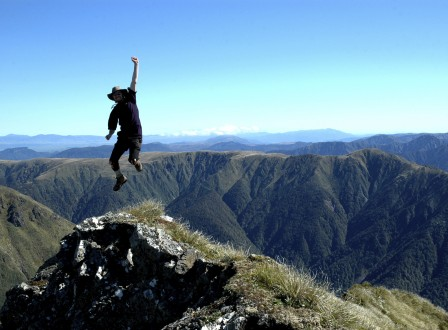 Man jumping at the top of a mountain with more mountains in the background
