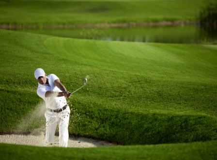 A man swinging a golf club, hitting the ball out of a sand bunker.